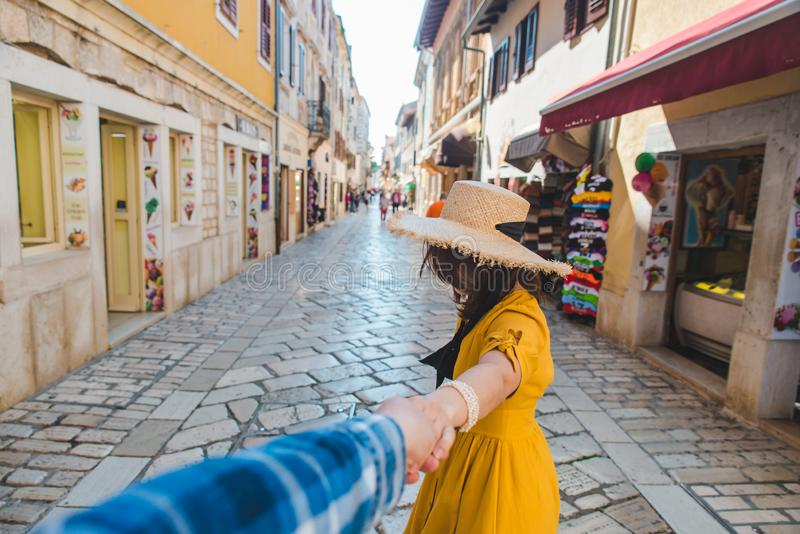 follow me concept. woman in yellow sundress in straw hat walking forward by small resort city street holding man hand stock photos