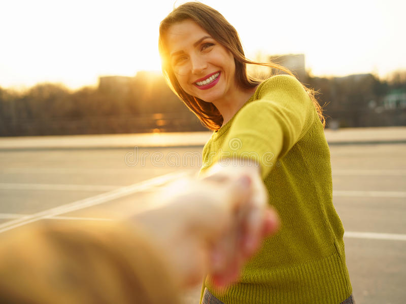 Follow me - happy young woman pulling guy`s hand - hand in hand stock photography