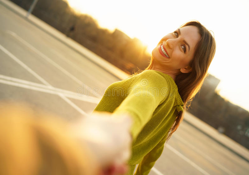 Follow me - happy young woman pulling guy`s hand - hand in hand royalty free stock photography