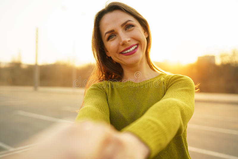 Follow me - happy young woman pulling guy`s hand - hand in hand stock image