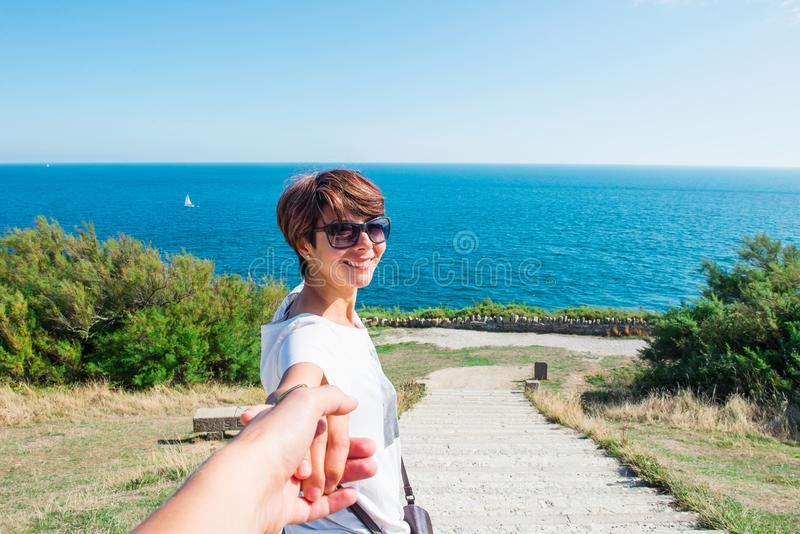 Follow me. Portrait of Cheerful smiling young woman in sunglasses holding man by hand and walking through park trail to the sea. T royalty free stock images