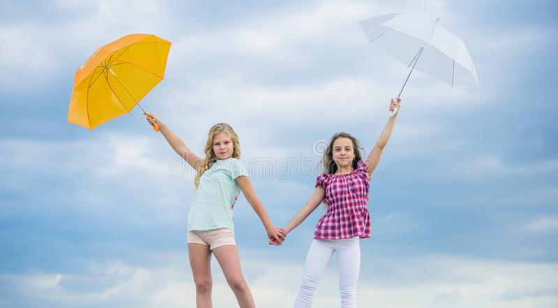 Follow me. school time. autumn season. rainy weather forecast. fall kid fashion. Feeling protected at this autumn day. Happy small girls with umbrella royalty free stock photography