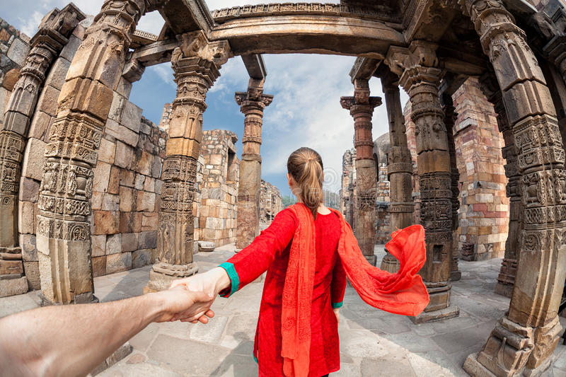 Follow me to Qutub Minar. Woman in red costume with scarf leading man by hand to Qutub Minar tower in Delhi, India royalty free stock images