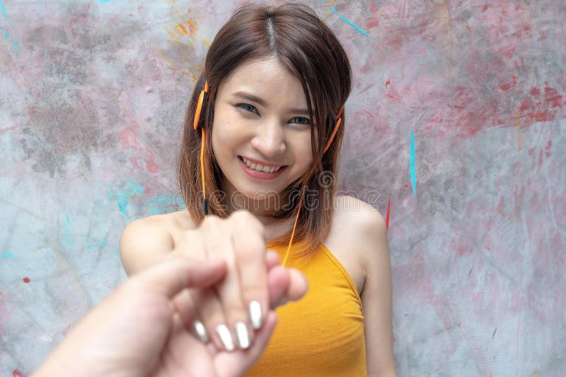 Follow me. Young woman holding boyfriend hand with happy face. Smiling asian girl listening music with headphone over colourful royalty free stock photos