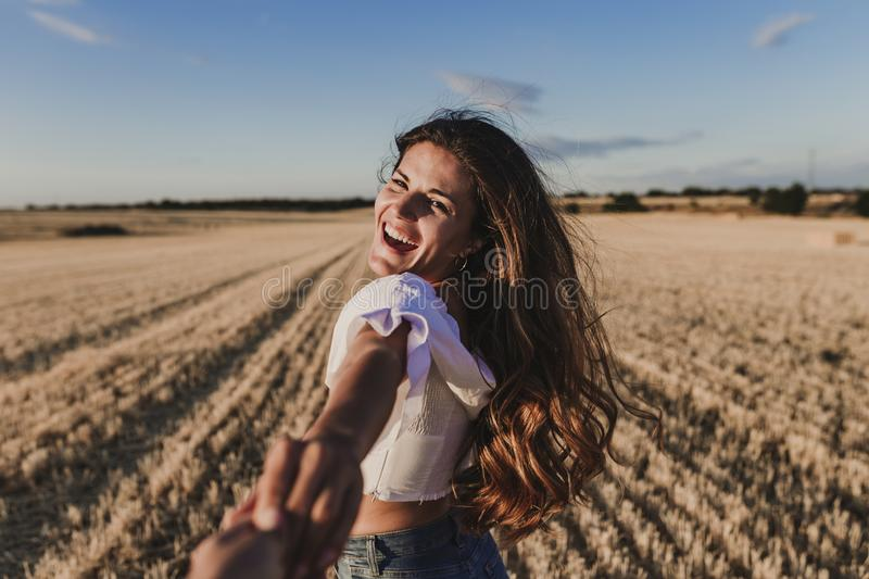 Follow me. Young woman holding hand and leading man to the beautiful nature sunset yellow landscape. View from back side, POV. royalty free stock photos