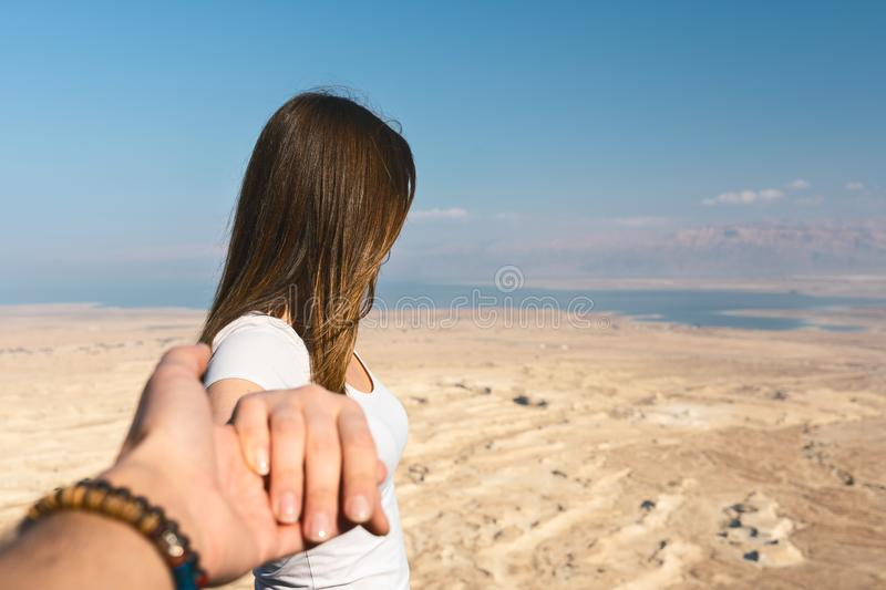 Follow me concept. young woman looking the desert in Israel. Follow me of a young woman on a mountain over the Dead Sea and the desert of Israel royalty free stock photography