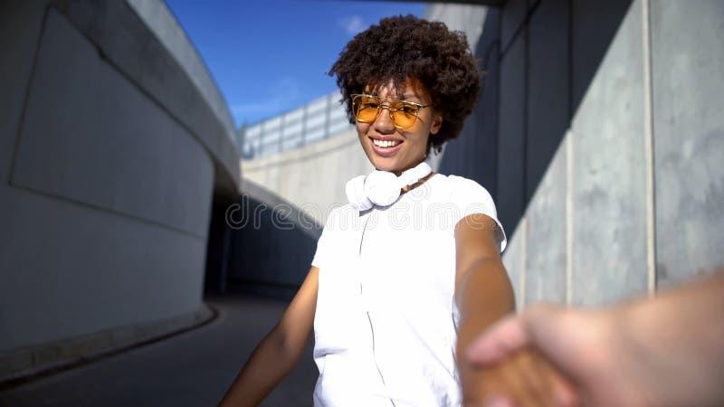 Follow-mepaare, schöne afroe-amerikanisch Frau, welche die Kamera, reisend betrachtet stockfotografie