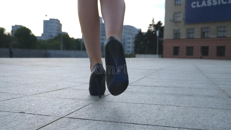 Follow to female legs in high heels shoes walking in the urban street. Feet of young business woman in high-heeled royalty free stock photo