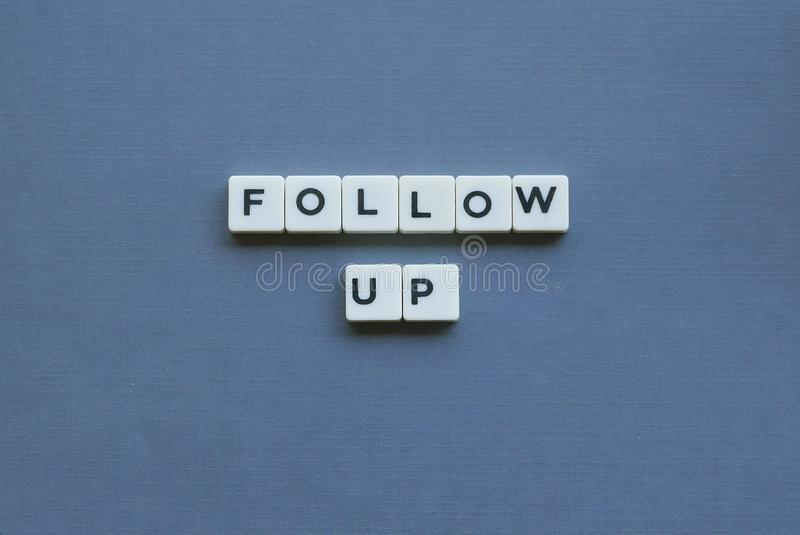 ' Follow Up ' word made of square letter word on grey background stock photography