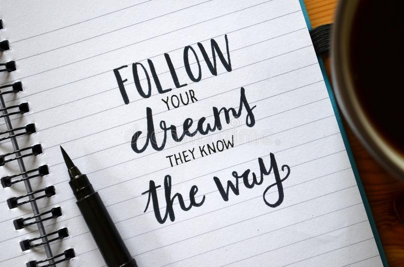 FOLLOW YOUR DREAMS THEY KNOW THE WAY hand-lettered in notebook stock images