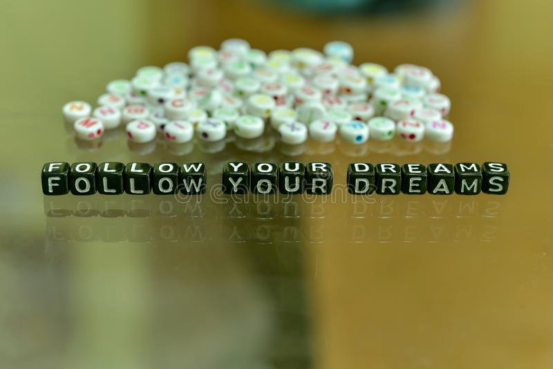 FOLLOW YOUR DREAMS  written with Acrylic Black cube with white Alphabet Beads on the Glass Background.  stock photography