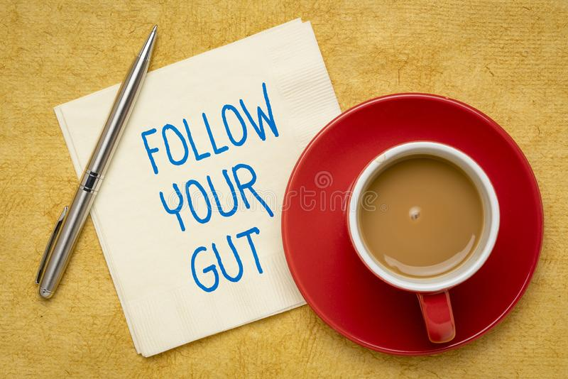 Follow your gut reminder. Handwriting on a napkin with a cup of coffee stock photo