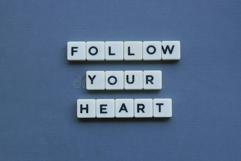 ' Follow Your Heart ' word made of square letter word on grey background. Intuition, concept, motivation, emotion, passion, love, inspiration, advice stock image