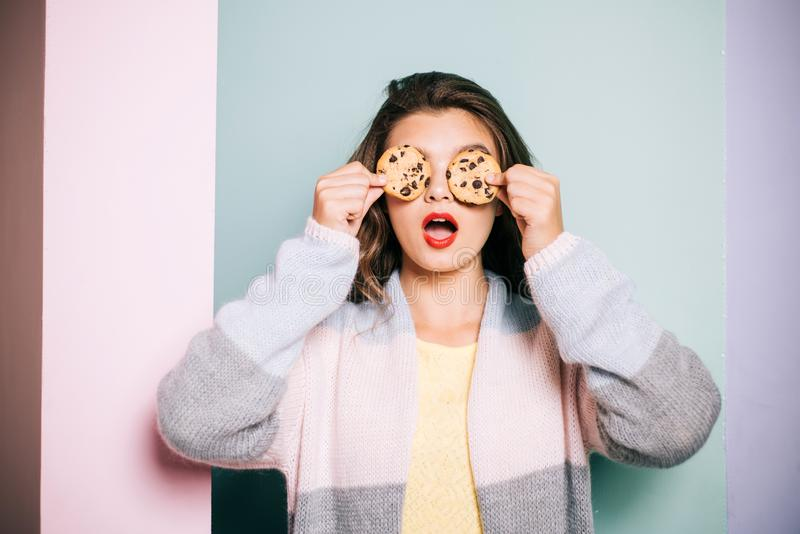 Following a cooking recipe. Pretty girl covering eyes with cookies. Cute girl having fun with cookies. Bakery style. Chocolate chip cookie recipe. Bakery shop royalty free stock photos