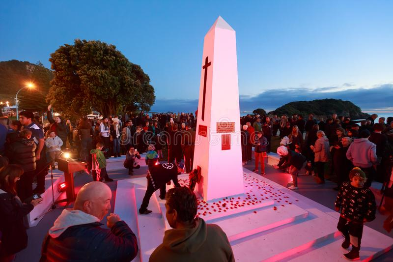 Anzac Day 2018, Mount Maunganui NZ: People lay poppies around the base of the cenotaph royalty free stock photography