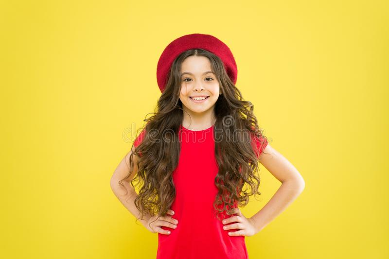 Following her personal style. little girl in french style hat. happy girl with long curly hair in beret. parisian child royalty free stock image