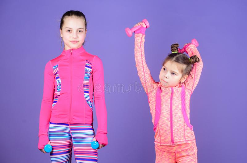 Following her sister. Girls cute kid exercising with dumbbells. Motivation and sport example concept. Toddler repeat. Exercise after sister. Sport exercises for stock photo
