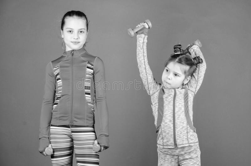 Following her sister. Girls cute kid exercising with dumbbells. Motivation and sport example concept. Toddler repeat. Exercise after sister. Sport exercises for stock photography