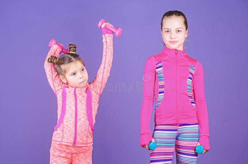 Following her sister. Girls cute kid exercising with dumbbells. Motivation and sport example concept. Toddler repeat. Exercise after sister. Sport exercises for royalty free stock photo
