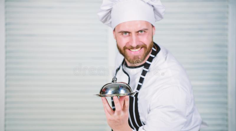 Following his favorite recipe. Chef cook in uniform standing with delicious dish. Master chef serving meal in restaurant. Handsome man in apron and cook hat royalty free stock images