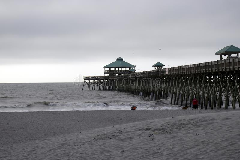 Folly Beach South Carolina, February 17, 2018 - waves rolling up beach next to boardwalk on and overcast day royalty free stock image
