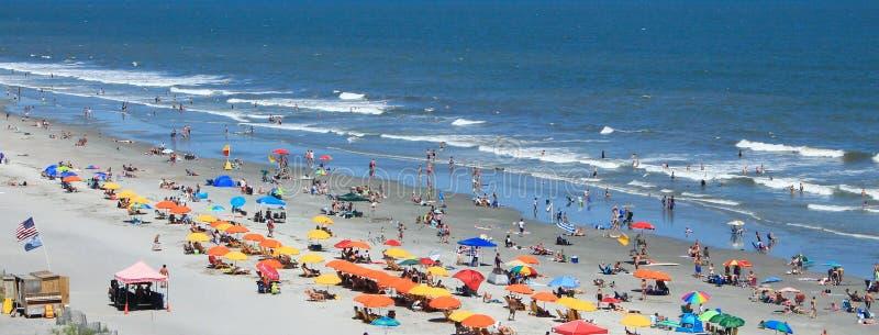Folly Beach Pier in SC sunbathers royalty free stock image