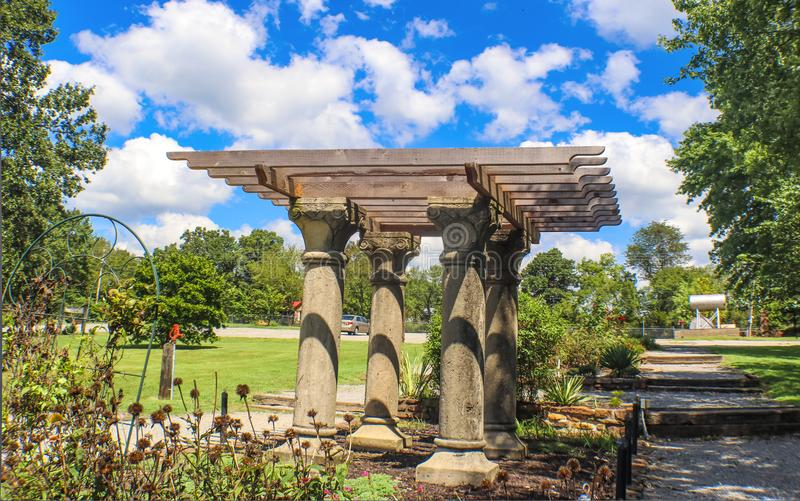 Folly or pavillion with rough facsimile of classical columns and wooden beams in an autumn park. With dead flowers stock photography