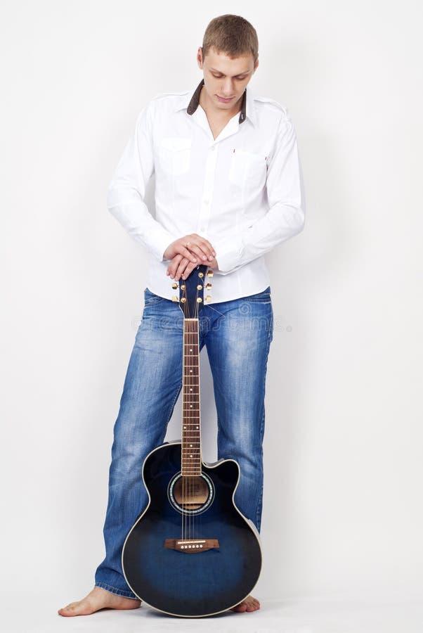 Folował długość młody człowiek z gitarą zdjęcie stock