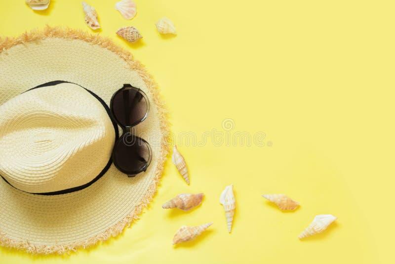 Foman ` s αχύρου καπέλο παραλιών και μαύρα γυαλιά ήλιων με τα θαλασσινά κοχύλια στο κίτρινο υπόβαθρο Τοπ όψη Επίπεδος βάλτε στοκ φωτογραφίες με δικαίωμα ελεύθερης χρήσης