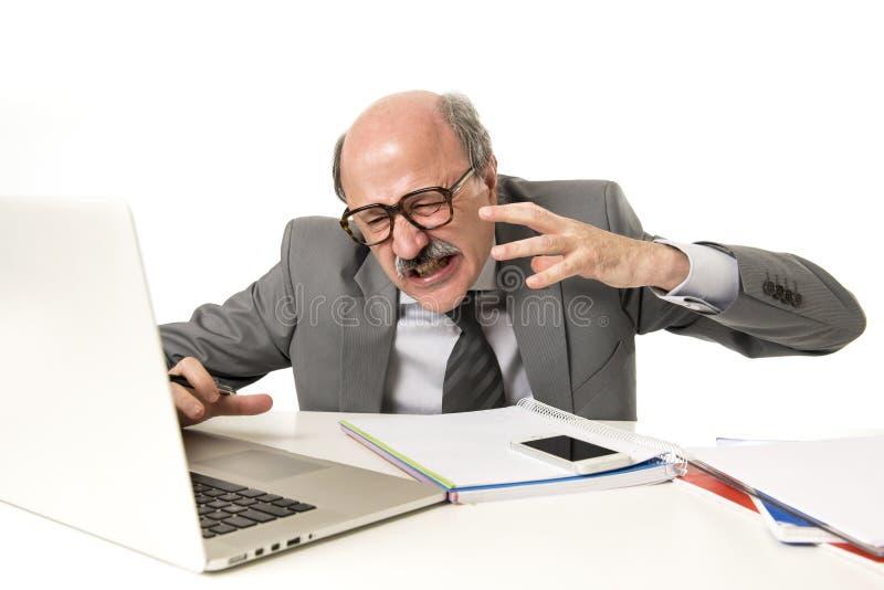 Fonctionnement chauve de l'homme 60s d'affaires soumis à une contrainte et frustré au bureau d'ordinateur portable d'ordinateur d photos stock