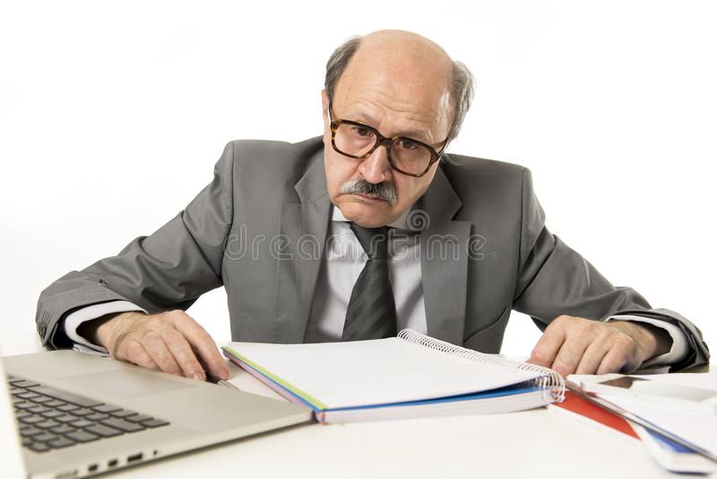 Fonctionnement chauve de l'homme 60s d'affaires soumis à une contrainte et frustré au bureau d'ordinateur portable d'ordinateur d images libres de droits