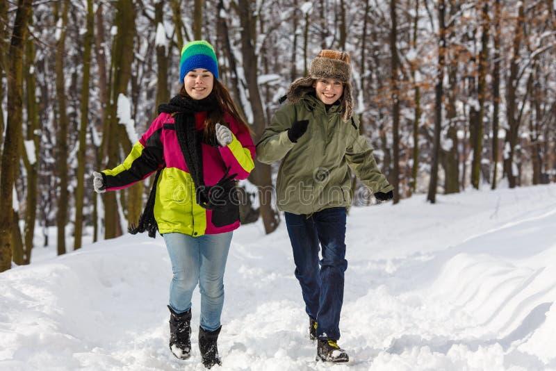 Fonctionnement d'adolescent et de fille extérieur en parc d'hiver photo libre de droits