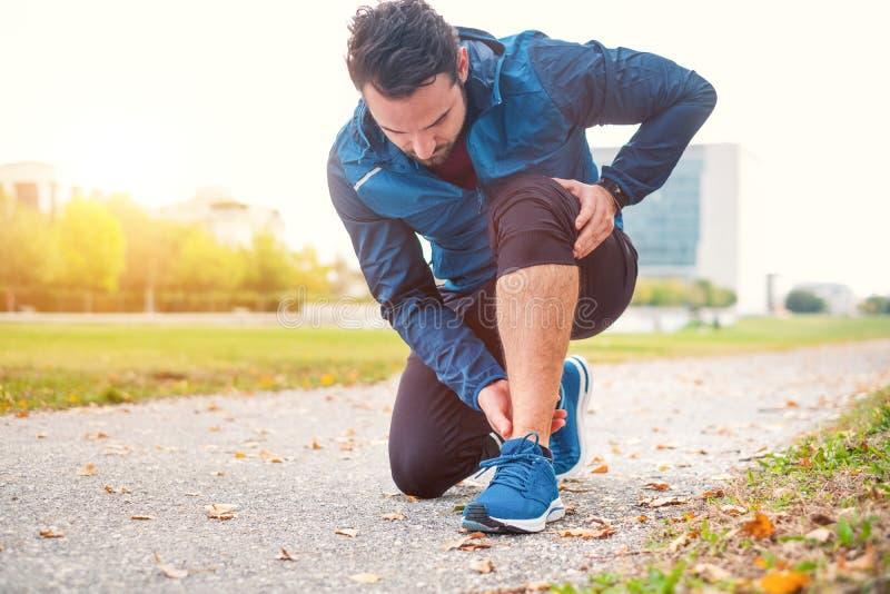 Fonctionnement d'athlète extérieur et souffrance pour la douleur de ligament de cheville images libres de droits