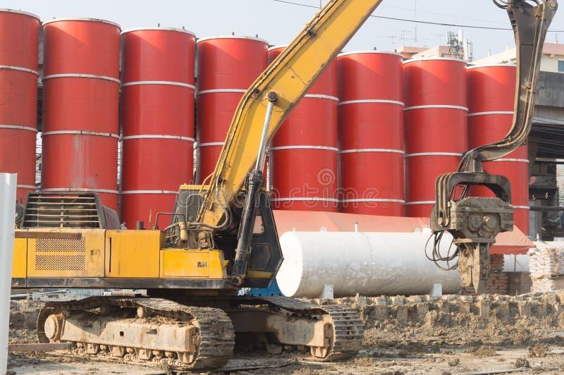 Fonctionnement d'excavatrice près des réservoirs de solution de forage rouges au chantier de construction de la station de métro  images libres de droits