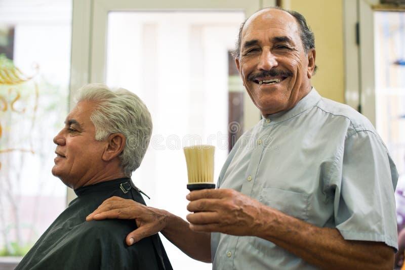 Fonctionnement d'homme aîné comme coiffeur dans le salon de cheveu photographie stock