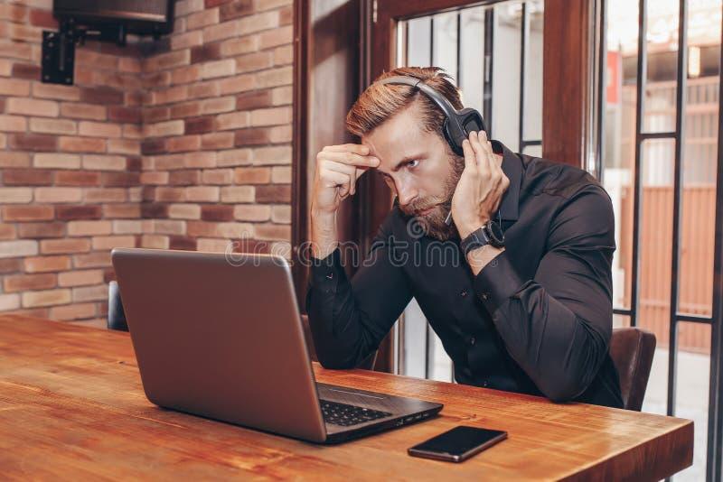 Fonctionnement d'homme d'affaires essayant de résoudre des problèmes en ligne avec l'ordinateur portable image stock