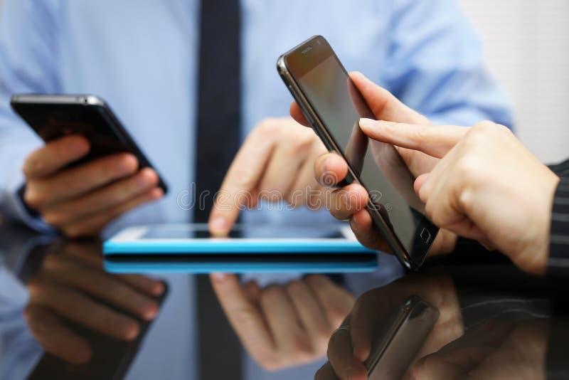 Fonctionnement d'homme d'affaires et de femme d'affaires et utilisation du pho mobile futé photo stock