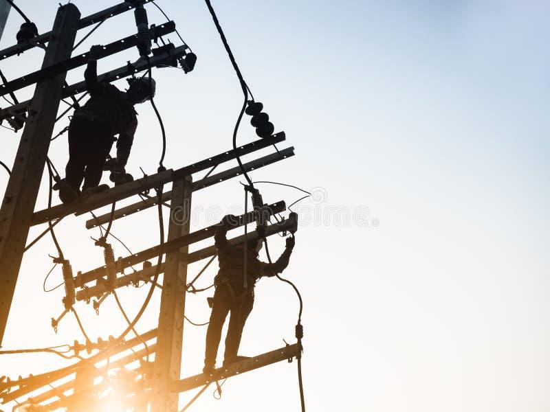 Fonctionnement d'homme de silhouette de travail de réparation de monteur de lignes de ligne électrique de l'électricité photographie stock