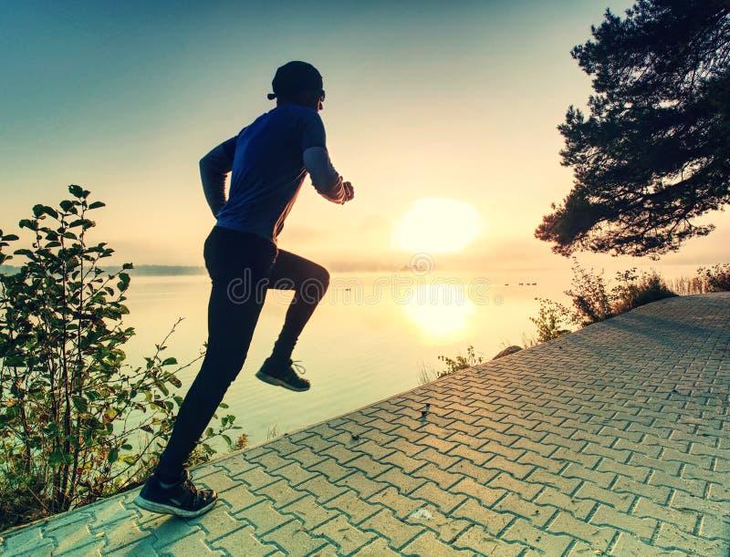 Fonctionnement d'homme sur le trottoir de rivage de lac pendant le lever de soleil ou le coucher du soleil photos stock
