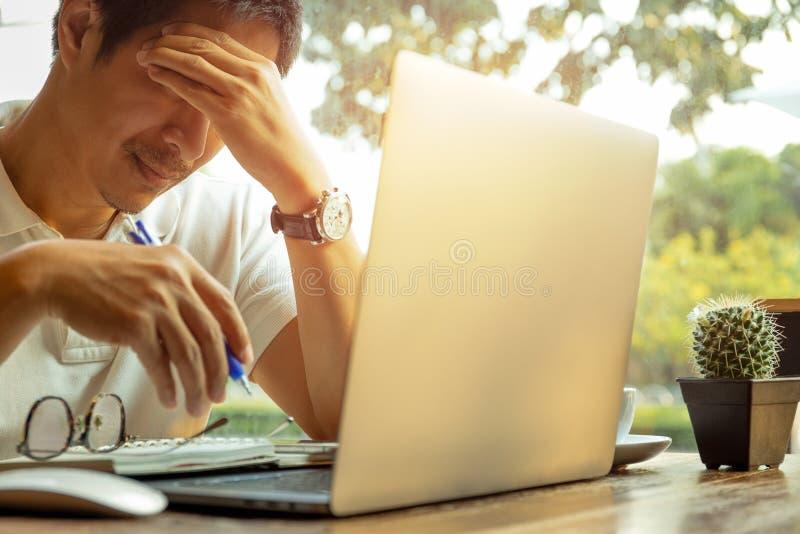 Fonctionnement de dépression d'homme d'affaires sur l'ordinateur portable avec la main tenant sa tête image stock