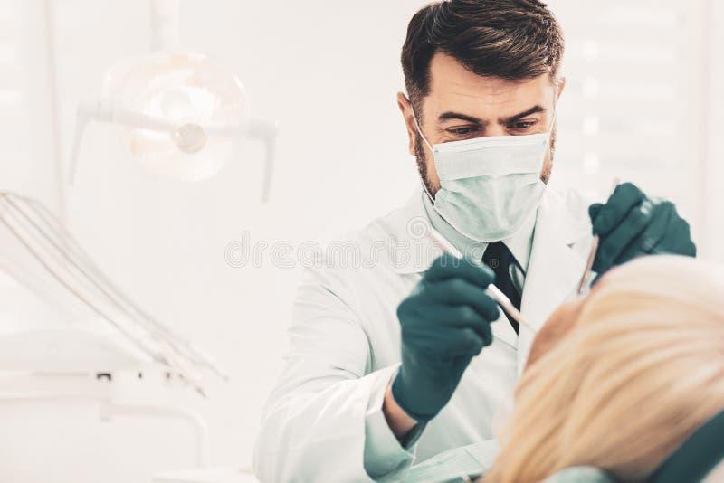 Fonctionnement de dentiste avec des dents de clients image stock