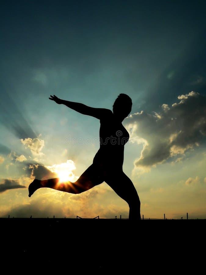 Fonctionnement de femme, contre le coucher du soleil image stock