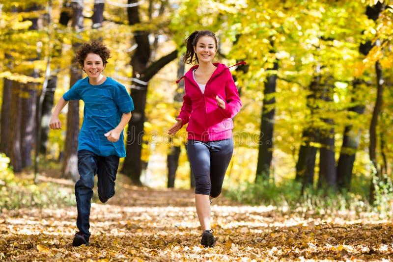 Fonctionnement de fille et de garçon, sautant en parc images stock