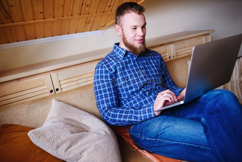 Fonctionnement de jeune homme absorbé sur l'ordinateur portable à la maison photo libre de droits