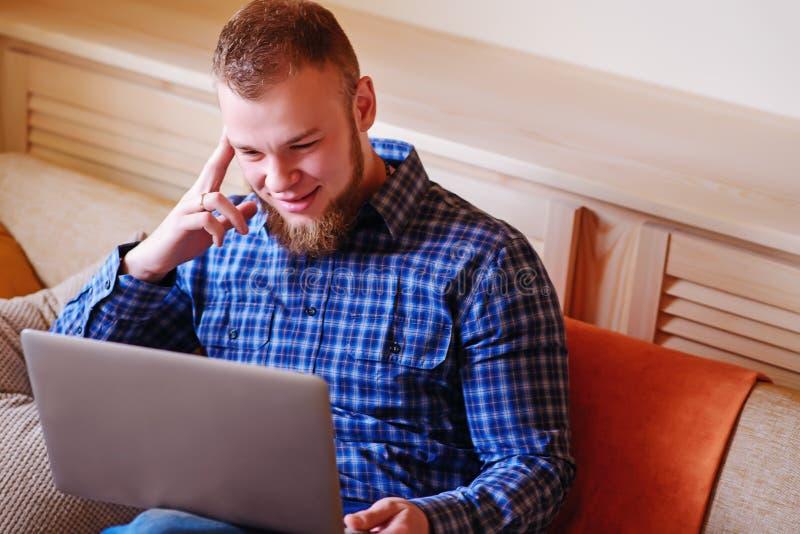 Fonctionnement de jeune homme absorbé sur l'ordinateur portable à la maison photographie stock