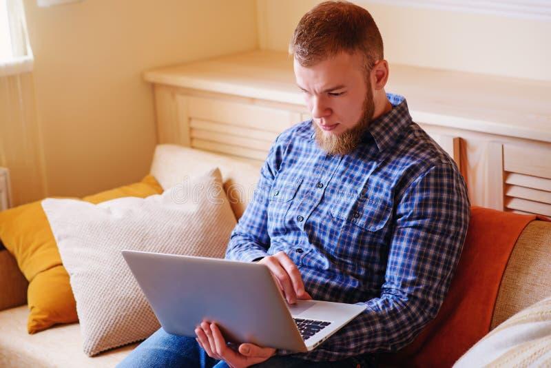 Fonctionnement de jeune homme absorbé sur l'ordinateur portable à la maison photo stock