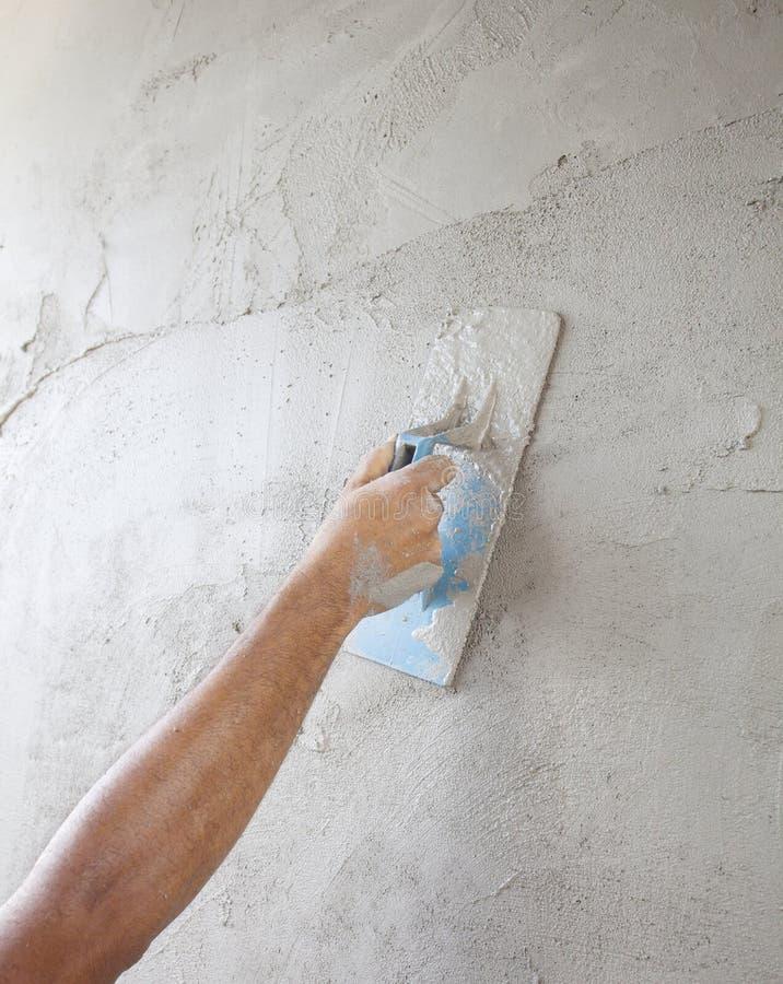 Fonctionnement de main de travailleur au mur construit de ciment de la construction à la maison images libres de droits