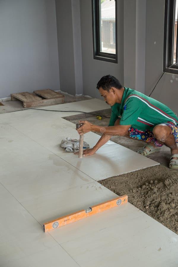 Fonctionnement de travailleur carrelé au chantier de construction photographie stock libre de droits