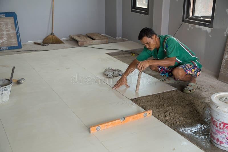 Fonctionnement de travailleur carrelé au chantier de construction photographie stock
