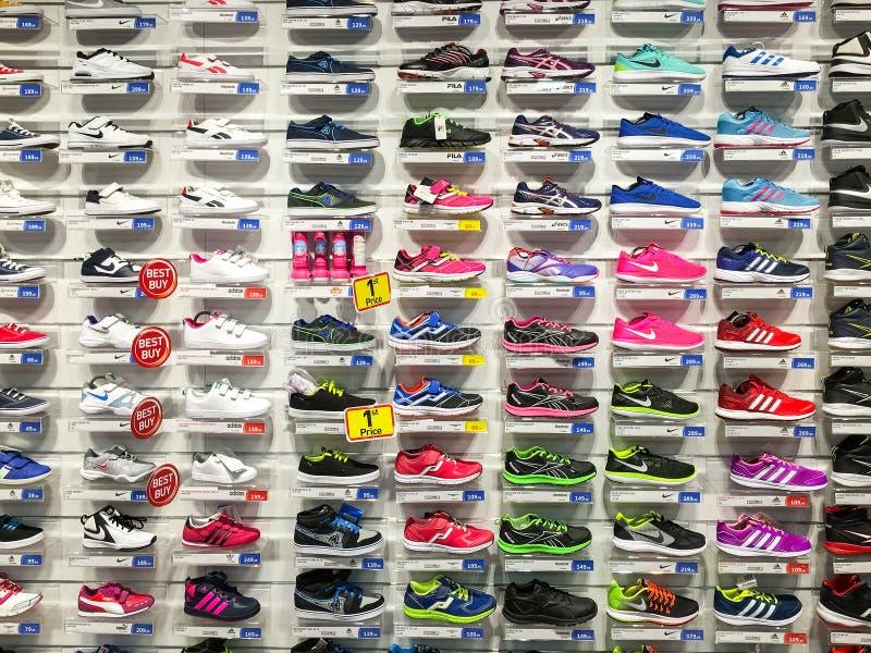 Fonctionnement et chaussures de sport à vendre dans l'affichage de magasin de chaussures d'habillement de mode photographie stock